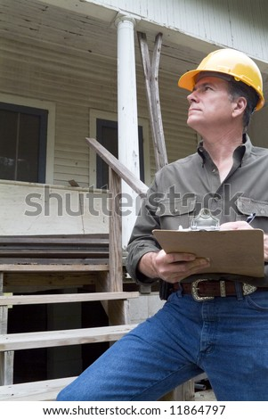 A man in a hard hat standing in front of an old rundown house holding a clipboard in his hand. - stock photo