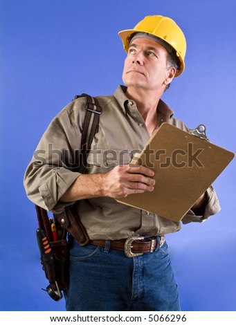 A man in a hardhat, with a tool belt on his arm, looking upward. - stock photo