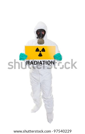 A man in a  hazmat suit holding a sign