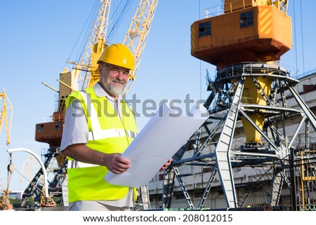 a man in a helmet in the port holding drawings