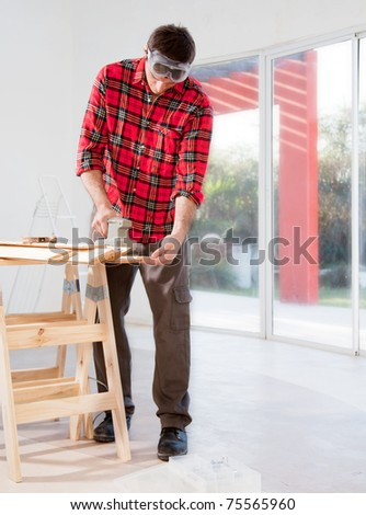 A man in a home interior sanding wood with an electric hand sander - stock photo