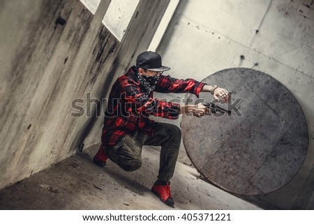 A man in a mask holds gun. - stock photo