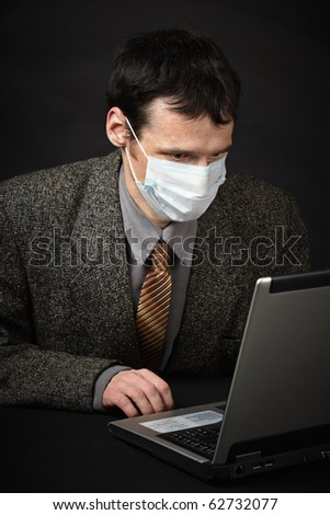 A man in a medical mask diagnoses computer - stock photo