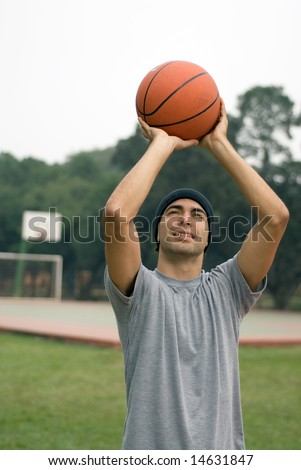 A man, in a park, ready to shoot a basketball, standing tall and half-smiling - vertically framed - stock photo