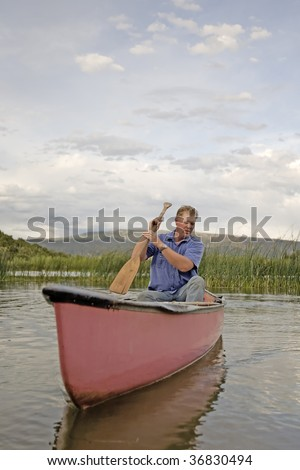 A man in a red canoe with his paddle.