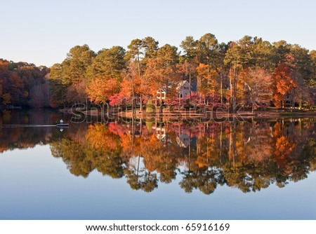 A man in a small boat on a calm lake in autumn