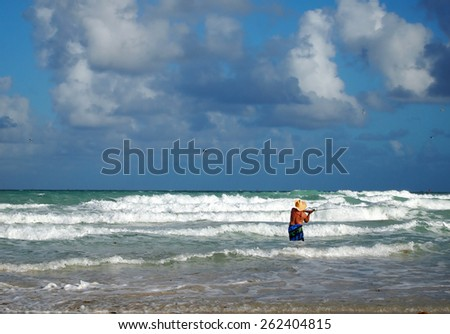 A man in a straw hat casts his fishing line out into the surf while standing in the breakers on the beach.  - stock photo