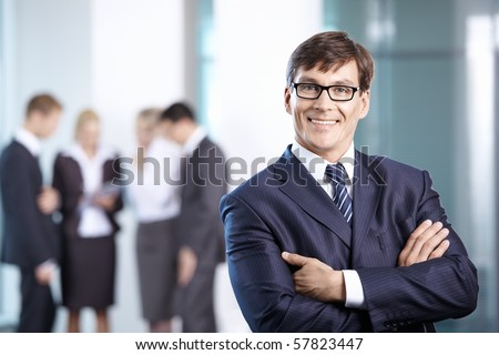 A man in a suit against the office workers - stock photo