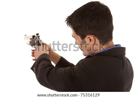 A man in a suit is holding a gun and looking down it. - stock photo
