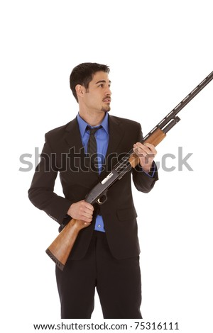 A man in a suit is holding a shotgun.