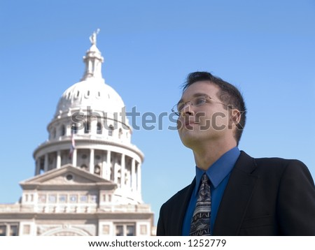A man in a suit looking out over the Texas State Capitol. - stock photo