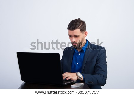 A man in a suit sitting at a laptop