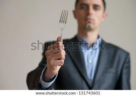 A man in a suit with a fork in his hand - stock photo