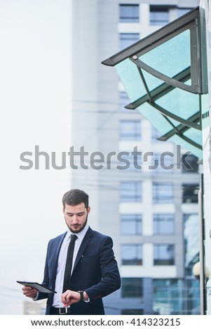 A man in a suit with a tablet in hand looking at the clock on the background of the building with a glass facade