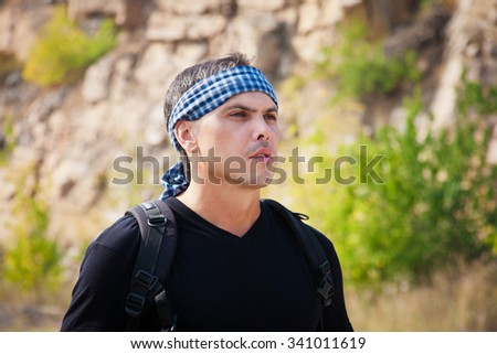 A man in a t-shirt and a bandanna on nature on a sunny day