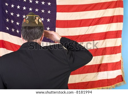 A man in a VFW cap saluting an old faded 48 star American flag.