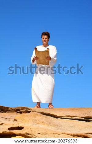 A man in a white robe reads from a scroll in a hot and sunny rocky desert landscape - stock photo