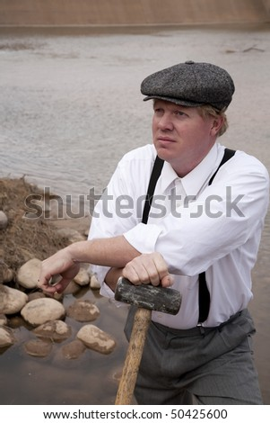 a man in a white shirt leaning on a big hammer resting