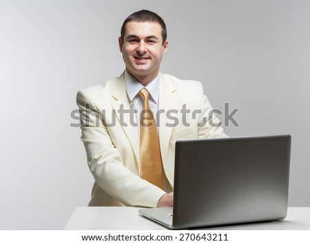 A man in a white suit sitting with a laptop. Makes hand gestures. Vivid emotions.