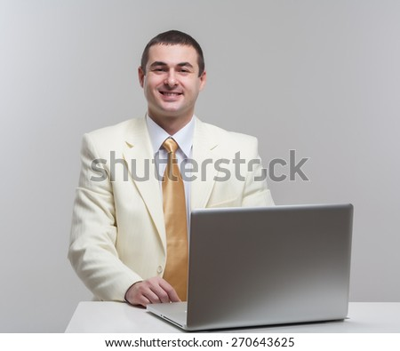 A man in a white suit sitting with a laptop. Makes hand gestures. Vivid emotions. - stock photo