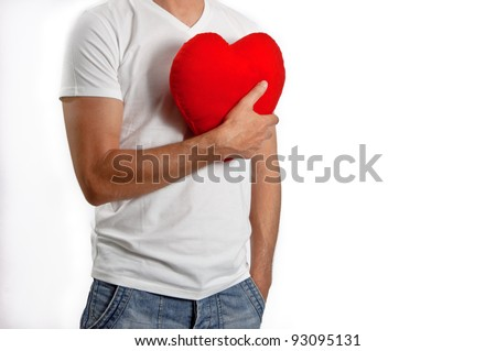 A man in a white T-shirt holding a Red Heart to his chest