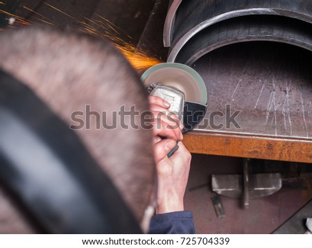 A man in a workshop using an industrial metal grinder to grind down stainless steel, creating vibrant orange sparks
