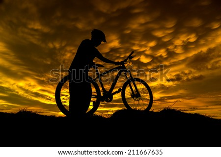 a man in action with bicycle during sunset - stock photo