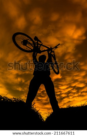 a man in action with bicycle during sunset. vertical format - stock photo