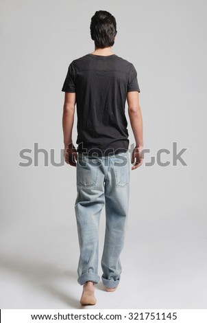 a man in back walking in a studio photo - stock photo