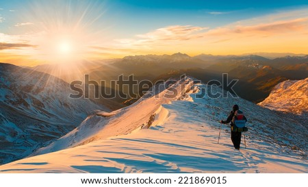 A man in beautiful  mountain sunset winter landscape  snow background, adventure hobby extreme tracking  ice Christmas ski new Year amazing fresh - stock photo