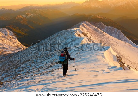 A man in beautiful  mountain sunset winter landscape  snow background, adventure hobby extreme tracking - stock photo
