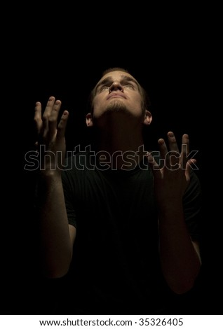 A man in black looking up and pleading - stock photo