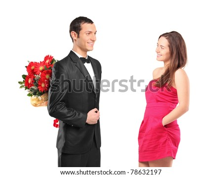 A man in black suit hiding bouquet of flowers from a young woman isolated on white background - stock photo