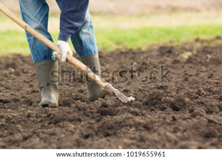 A man in boots digs the earth with a shovel