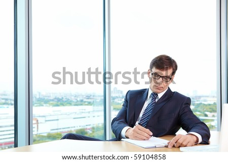 A man in business suit signs documents in the office - stock photo