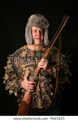 "a man in camoflauge and a furry hat holds an antique ""Flint Lock"" rifle"