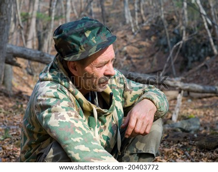A man in camouflage suit is in forest.