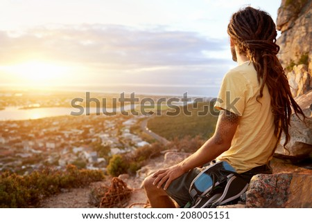 A man in dreadlocks on a mountain looking at the view with copyspace - stock photo
