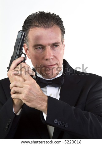 A man in formal attire holding an automatic pistol taken against a white background. - stock photo