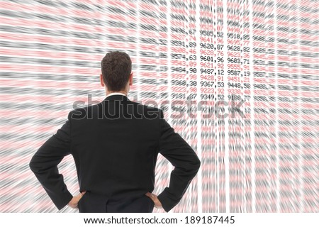 A Man in front of a big screen with numbers - stock photo