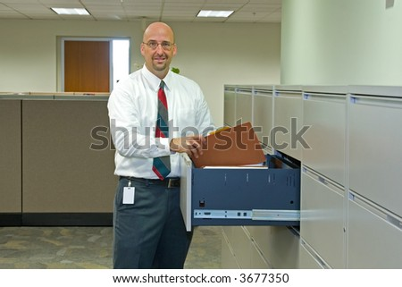A man in his corporate office environment, on the phone and at work - stock photo