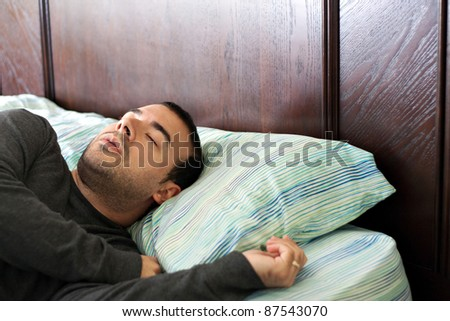 A man in his late 20s is fast asleep in bed.