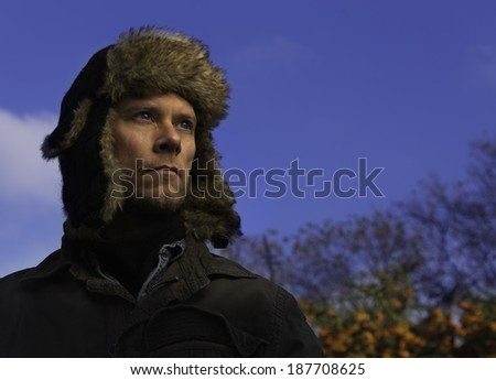 A man in his mid 30's wearing a jacket and fur hat on a bright winter's day. - stock photo