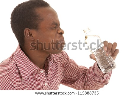 A man in his red plaid shirt with a funny expression on his face holding his water bottle - stock photo