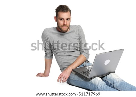 A man in his 20s sitting down on the floor with his laptop, wearing jeans and a grey shirt. White background.
