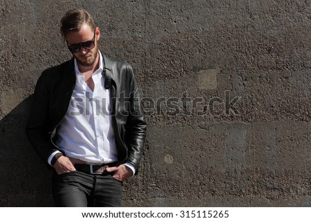A man in his 20s wearing a black leather jacket and white shirt, leaning back against a wall of stone on a sunny summer day,  - stock photo
