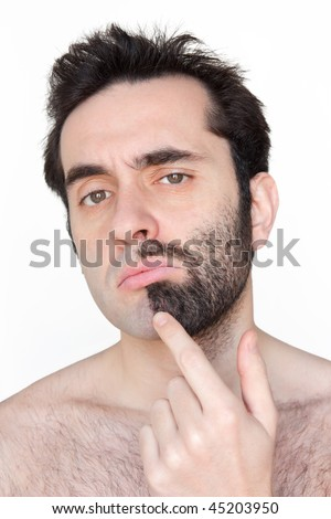 A man in his thirties with half face shaven, half face unshaven (beard), doubting about what to do. - stock photo