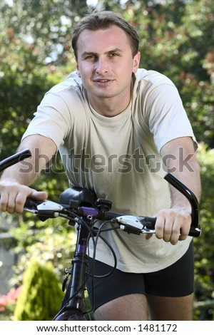 A man in his twenties staying by his bicycle.