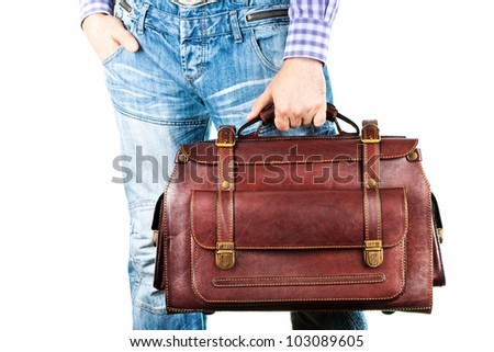 A man in jeans holding a brown leather travel bag in her hand (isolated on white background)