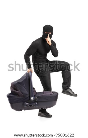 A man in robbery mask holding a carrycot with finger on the lips gesturing silence isolated on white background